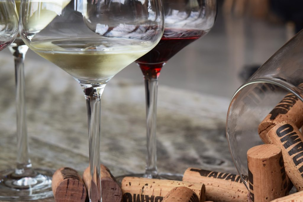 red and white wine in glasses with spilled corks